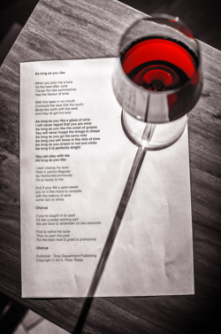Photo: still-life arrangement of the printed song text and a glass of red wine