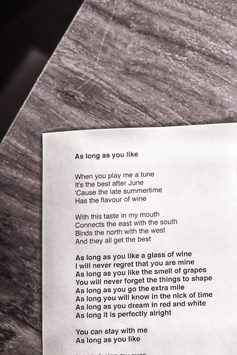 Photo: Detail of the still-life arrangement of the printed song text and a glass of red wine