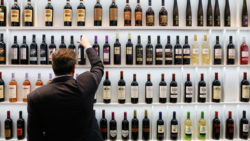 Photo: Man in front of shelf with wine bottles