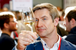 Man looking at white wine